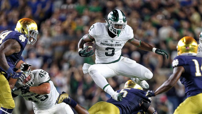 Michigan State Spartans running back LJ Scott (3) leaps over Notre Dame Fighting Irish linebacker Nyles Morgan (5) during the first half of Saturday night's game at Notre Dame Stadium.