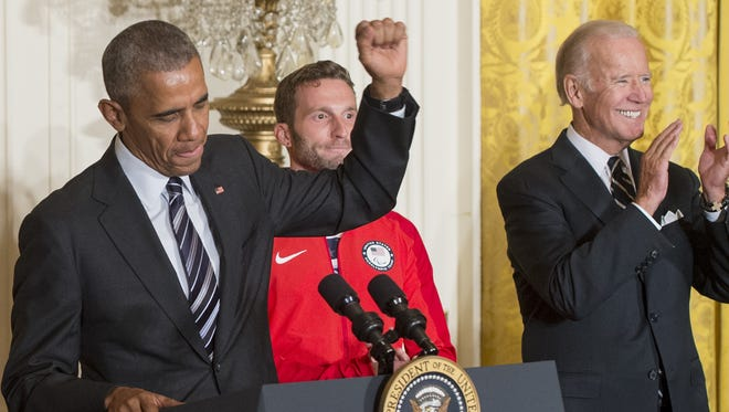 President Obama gestures alongside Paralympian Josh Brunais and Vice President Biden during a ceremony honoring the 2016 US Olympic and Paralympic teams during an event in the East Room of the White House Thursday.