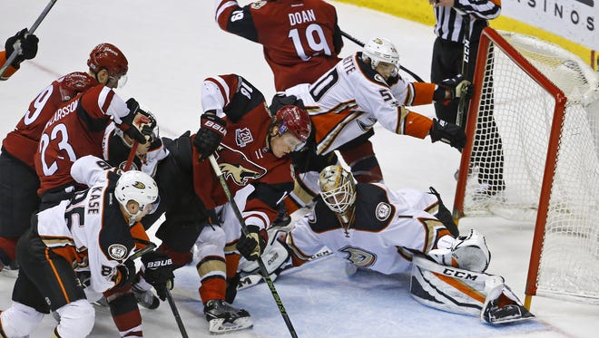 Arizona Coyotes center Christian Dvorak (18) tries to slip the puck past Anaheim Ducks goalie Jonathan Bernier (1) as center Antoine Vermette (50) knocks the net  over in the third period of their NHL game Saturday, Jan. 14, 2017 in Glendale, Arizona.