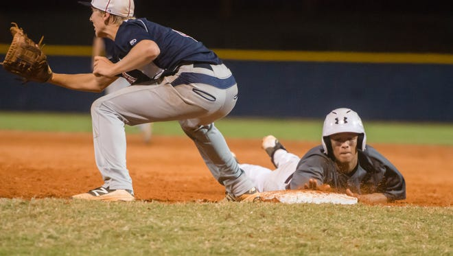 Astronaut High's Daemon Woodruff safely slides back to first during a game against Cocoa Beach Jr/Sr High.