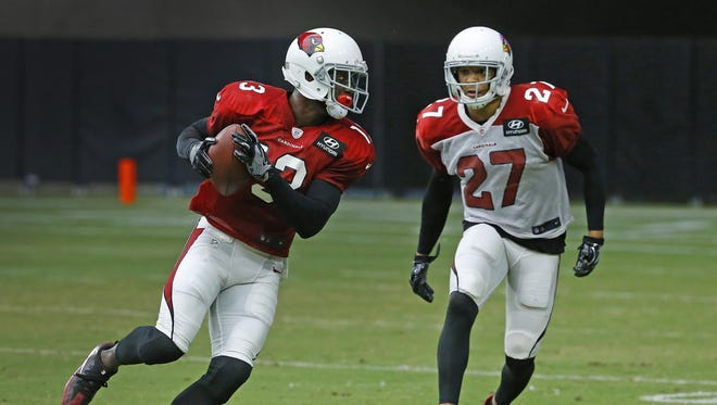Cardinals wide receiver Jaron Brown (13) makes a catch in front of defensive back Tyvon Branch (27) during training camp on Monday.