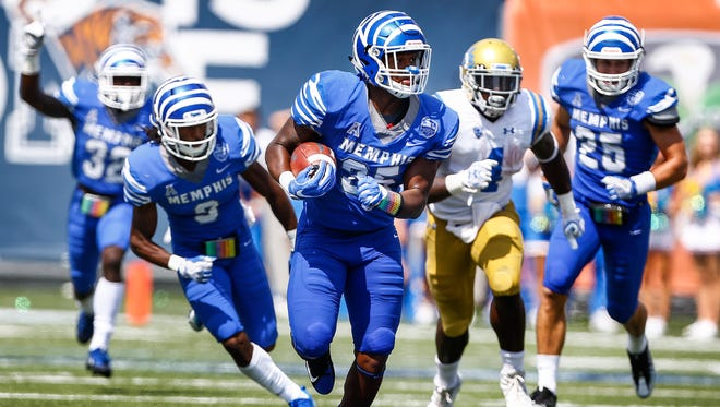 University of Memphis linebacker Tim Hart, middle, returns an interception for a touchdown against UCLA during third-quarter action at Liberty Bowl Memorial Stadium in Memphis on Sept. 16, 2017.