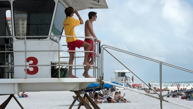 Pensacola Beach Lifeguards, Ben Quarles, and Kelly Kennedy keep a watchful eye on beachgoers from tower three at Casino Beach Sunday, Oct. 15, 2017. Sunday marks the last day the lifeguards will man the structures this season. On Monday, Oct. 16, 2017, the lifeguards will switch to roving patrols with limited personnel, and the towers removed for winter storage.
