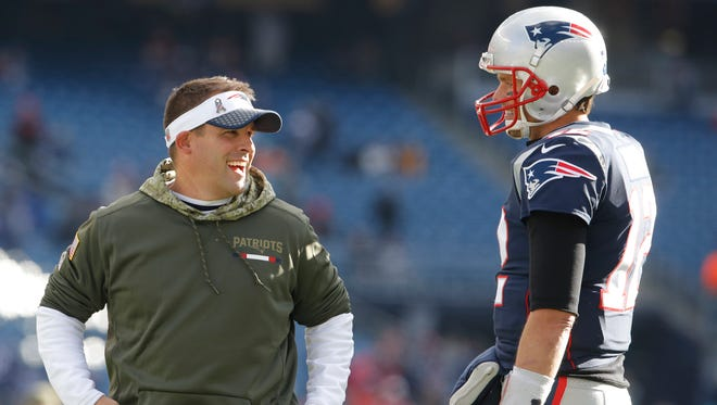 New England Patriots quarterback Tom Brady (12) talks with offensive coordinator Josh McDaniel before the game against the Miami Dolphins at Gillette Stadium.