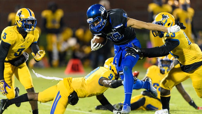 Chandler's Gunner Romney (#18) breaks tackles by Northwestern's Larry Robbins (#9) and Aaron Louis (#23) in the second quarter of the 2017 GEICO State Champions Bowl Series football game on Saturday, Dec. 23, 2017, at Grand Canyon University in Phoenix, Ariz.