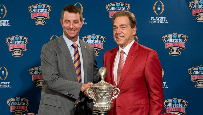 Clemson head coach Dabo Swinney  and Alabama head coach Nick Saban pose with the trophy during the Sugar Bowl coaches press conferences in New Orleans, La. on Sunday December 31, 2017. =