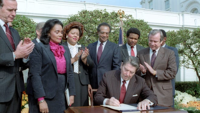 President Reagan signs legislation in the Rose Garden for the Martin Luther King Holiday with Vice President George Bush, left, Coretta Scott King, Rep. Katie Hall, (D-Ind.) Samuel Pierce, Secretary of the HUD; J. Steven Rhodes, the vice president's domestic policy assistant; and Senator Howard Baker of Tennessee look on.