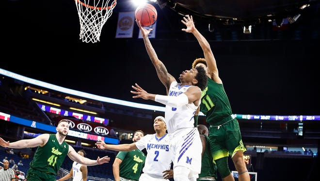 Memphis guard Kareem Brewton Jr. (front) drives for a layup against the USF defense in the AAC tournament last season.