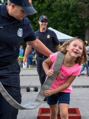 Elayna Vaughn, 7 years-old, pulls a weight with a firehose,