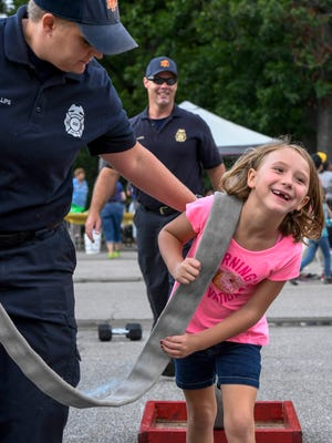 Elayna Vaughn, 7 years-old, pulls a weight with a firehose, with a little help from firefighter Jamie Phillips, at the Children's Firefighting Challenge Course at the Vanderburgh County National Night Out event held in Wesselman Park Tuesday, August 1, 2017.