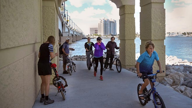 Bicyclists ride the Lake Trail built under the new Flagler Memorial Bridge.