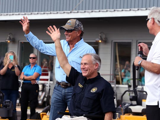 George Strait (left) and Texas Governor Greg Abbott wave to the crowd in Rockport, TX, on Thursday, September 21, 2017 to visit with individuals affected by Hurricane Harvey.