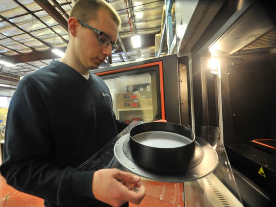 Product development engineering Nathan Fetting, 28, of Wausau, inspects a prototype made from a 3D printer Thursday, April 2, 2015, at Greenheck Fan Corporation in Schofield.