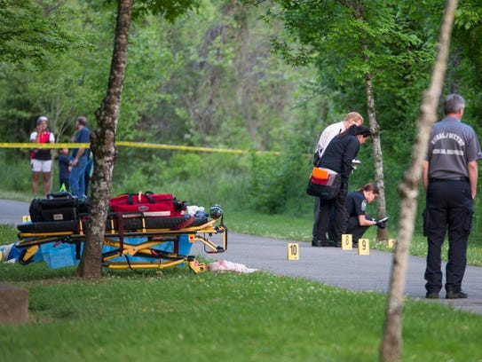 Police look for clues at the scene of the murder of