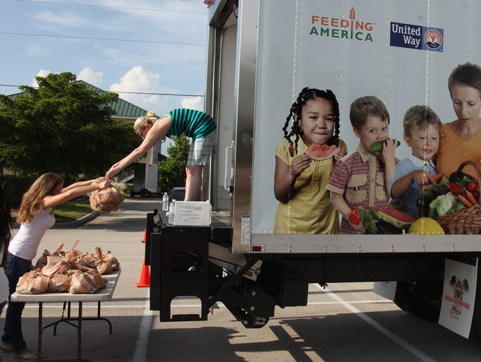 Volunteers Ashley Lavelle, Sarah Prater, and Laquitta Latson remove bags of perishable food from a refrigerated truck that was purchased by the Harry Chapin Food Bank from donations made by the Walmart Foundation State Giving Program
