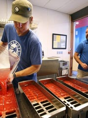 At MemPops on Ridgeway, Matt Starnes (left) pours a mix of watermelon and lemongrass into popsicle molds. Owner Chris Taylor is seen at right.