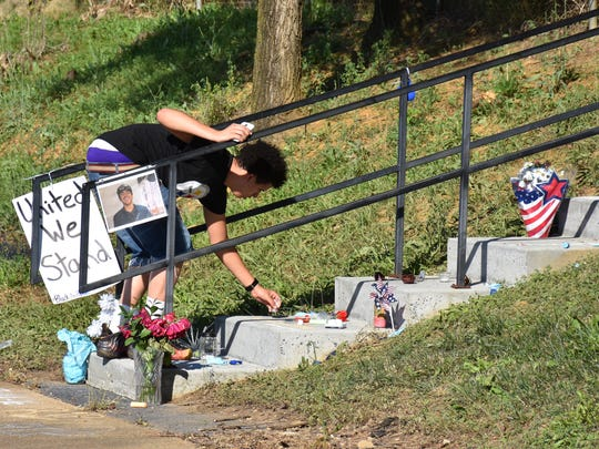 A teen from Harrisonburg places an item at an impromptu memorial at Kate Collins Middle School in Waynesboro for his friend, 17-year-old Orion Anthony Madden, who was slain. A group of teens, who didn't give their names, were at the site where Madden died on Sunday.
