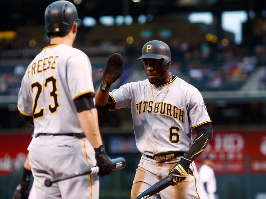 Pittsburgh Pirates' David Freese, left, congratulates Starling Marte after Marte scored on a single by Josh Bell off Colorado Rockies starting pitcher Jeff Hoffman in the first inning of a baseball game Friday, July 21, 2017, in Denver. (AP Photo/David Zalubowski)