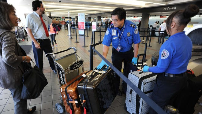 A departing passenger gives her luggage to TSA agents for security scanning.