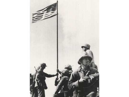 """Monticello native Earnest """"Boots"""" Thomas, sitting in the foreground holding a rifle, was part of the first unit photographed raising a flag after the battle of Iwo Jima. A photo of a second flag-raising became an iconic image of World War II. Thomas was killed eight days later, a week short of his 21st birthday."""