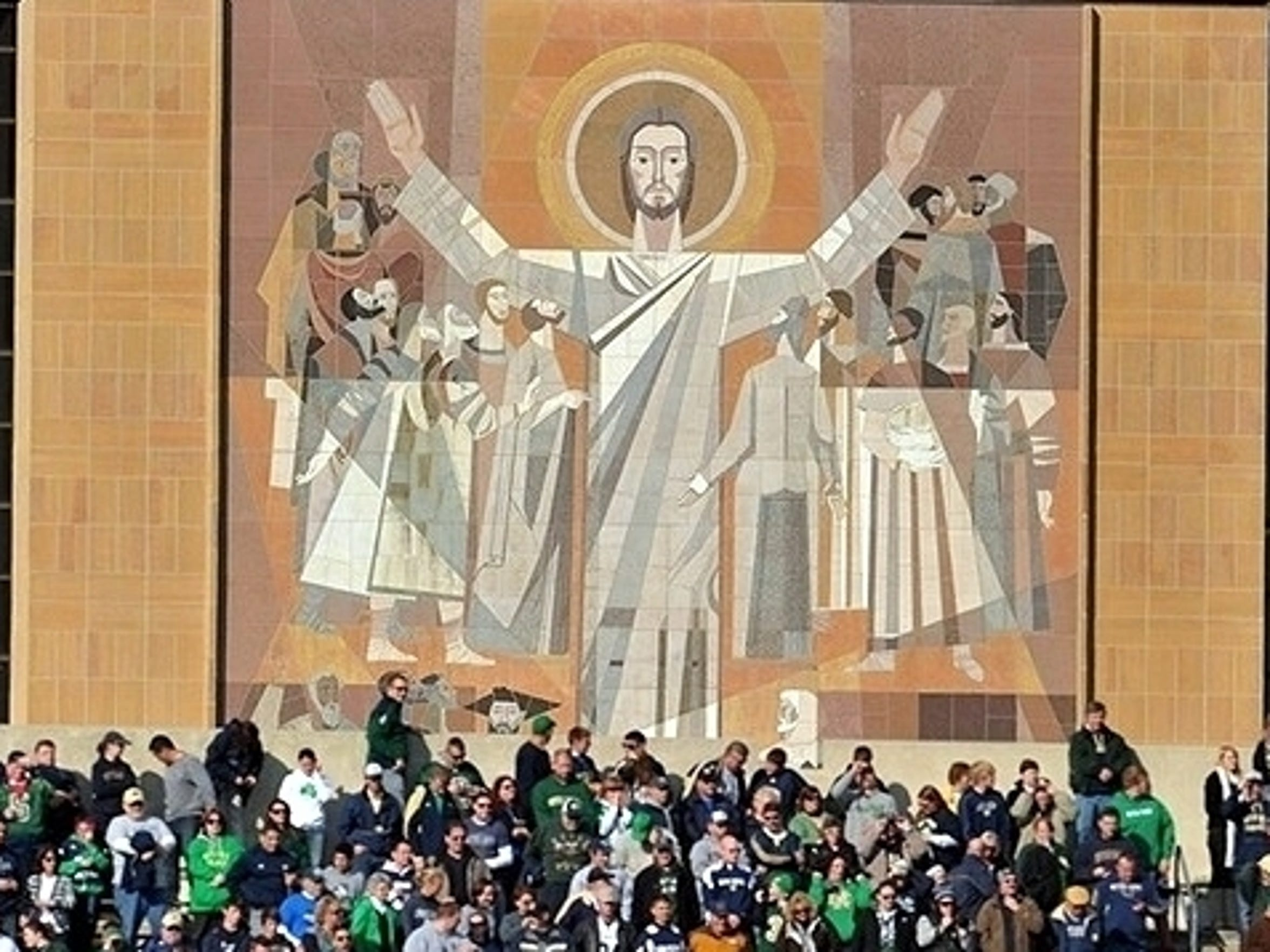 "Fans gather around ""Touchdown Jesus"" in South Bend. The university's Pastoral Plan for inclusion references John 4:7-8, which states ""anyone who fails to love can never have known God, because God is love."""