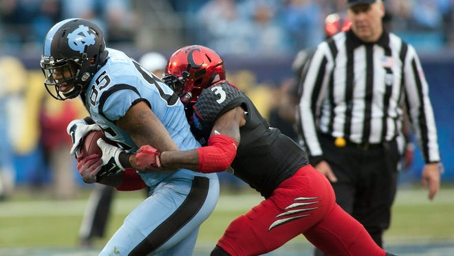 North Carolina tight end Eric Ebron tries to run out of the tackle of Cincinnati defensive back Howard Wilder.