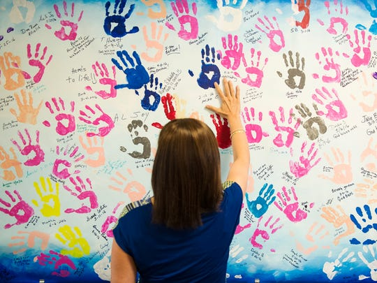 Rebecca Southard, of Owensville, leaves her handprint on the Hands of Hope wall after completing her final radiation treatment for breast cancer at Deaconess Gateway Hospital Women's Cancer Center in Newburgh, Thursday, Sept. 23, 2016.