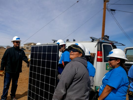 Fort Lewis College students test solar panels on Wednesday before installation at the Ojo Encino Chapter house.
