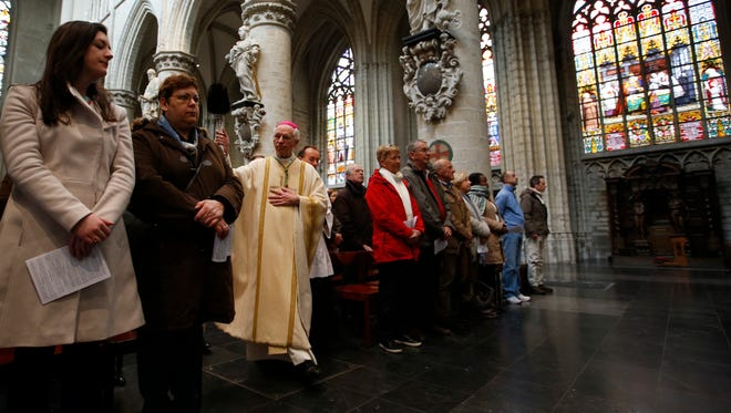 "Archbishop Jozef De Kesel sprinkles holy water on his congregation during Easter Sunday Mass at the Cathedral of St. Michael and St. Gudula in Brussels, on March, 27, 2016.  He said the recent Brussels attacks ""defy understanding."""