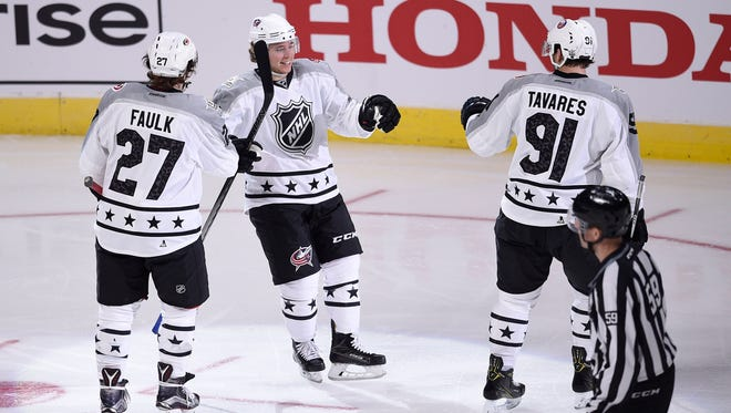 Metropolitan Division forward Cam Atkinson (13) of the Columbus Blue Jackets celebrates with forward John Tavares (91) of the New York Islanders and defenseman Justin Faulk (27) of the Carolina Hurricanes after a goal against the Pacific Division.