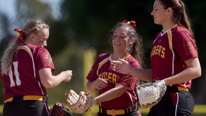 Roosevelt's Jasmine Schnider (left to right), Kylie Madrid  and Lexi Koltz high five in-between batters against Rapid City Central at Sherman Park Softball Complex.