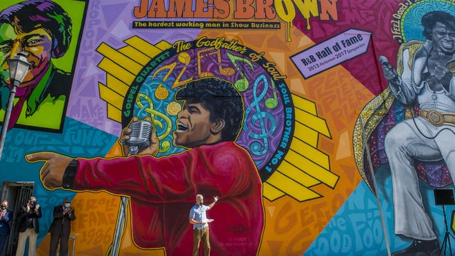 Artist Cole Phail, middle, talks about the James Brown mural he painted on the side of a building near the corner of 9th and Broad Streets in Augusta, Ga., Tuesday morning October 27, 2020.