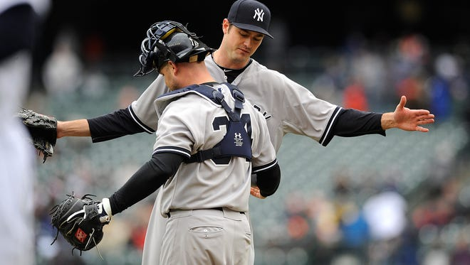 Yankees pitcher Andrew Miller celebrates with catcher Brian McCann after retiring three batters for the save Thursday.
