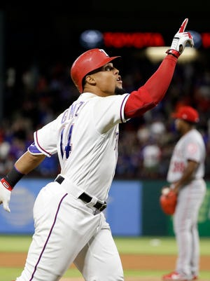 Texas Rangers' Carlos Gomez points skyward as he approaches the plate after hitting a two-run home run off of Los Angeles Angels relief pitcher Jose Valdez, rear, during the seventh inning of a baseball game in Arlington, Texas, on Saturday.