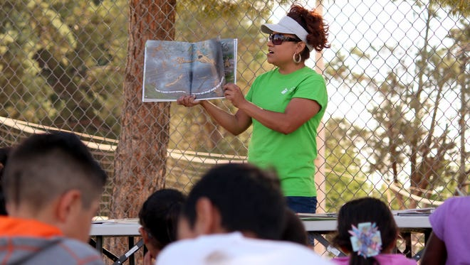 Sonia Moreno of the Children's Reading Foundation reads to a group of children during the City of Deming's Summer Youth Recreation Program at the Shedden Memorial Courts on Wednesday. Moreno's program promotes literacy and early childhood education in the community from the funding of a federal grant that will soon run out.