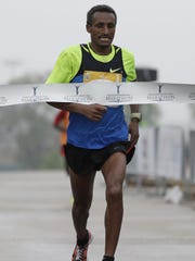 Teferi Regasa crosses the finish line to win the men's title in the Cellcom Green Bay Marathon on Sunday, May 21, 2017, in Green Bay.