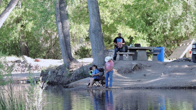 A family relaxes in the shade to try some fishing at Katfish Kove.