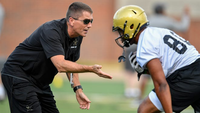 Vanderbilt offensive coordinator Andy Ludwig, left, works with players during the first practice of preseason camp Monday, July 31, 2017.