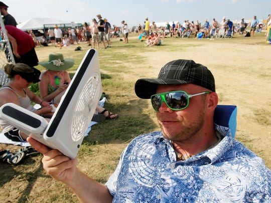 Clint Flaley of Celina, Tenn., cools off with a battery-operated fan during the John Fogerty show at the Bonnaroo Music & Arts Festival on June 13, 2010.