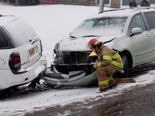Firefighter Daryl Pace inspects damage to a vehicle involved in a minor accident on Aurora Street Friday morning in Ithaca.