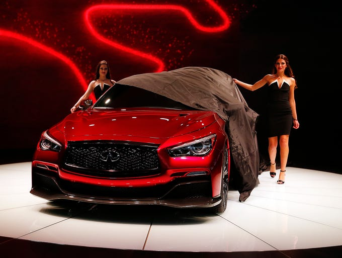 Models pull to sheet off to reveal the Infiniti  Eau Rouge performance version of the Q50 sedan at its unveiling at the North American International Auto Show in Detroit.