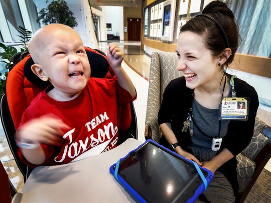 St. Jude Children's Research Hospital music therapist Amy Love (right) plays music on her iPad with patient Jaxson Harper, 3, who suffers from Rhabdomyosarcoma during a session at the hospital Thursday afternoon. Hospital patients who may need more than medical treatment for their life-threatening illnesses also benefit from the music therapy offered by Love, who sings, plays instruments and does other performances.