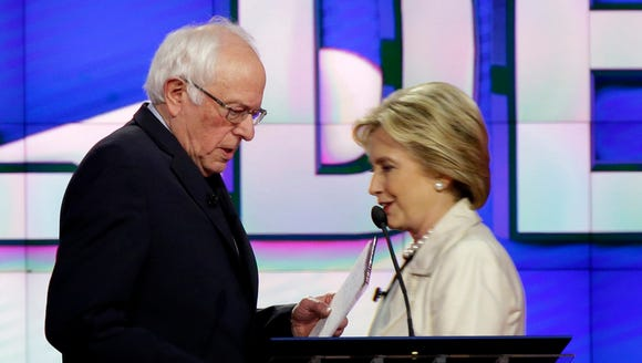 Bernie Sanders and Hillary Clinton pass during a break