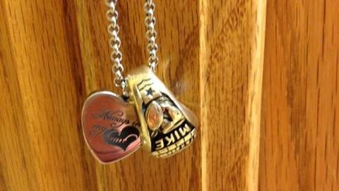 Melanie Elliot of Plymouth wears her brother's class ring on a necklace with a heart-shaped pendant containing some of her brother's ashes. Elliot recently was reunited with the class ring through a Facebook post.