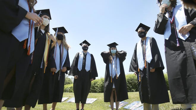 York High School seniors talk over details before their commencement Friday, June 12. Rather than hosting one large ceremony, the school hosted 11 smaller ones to minimize risk of transmitting COVID-19.