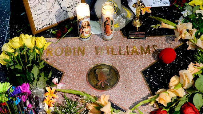 Flowers are placed Monday in memory of actor and comedian Robin Williams on his Walk of Fame star in the Hollywood district of Los Angeles. Williams, 63, died Monday at his San Francisco Bay Area home in an apparent suicide.