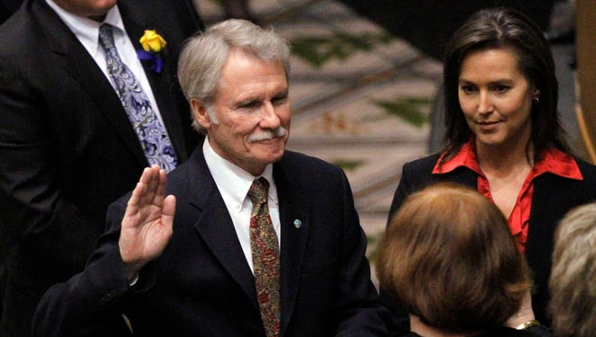 FILE--In this Jan. 10, 2011 file photo, Democrat John Kitzhaber, left, is sworn in as Oregon governor while Cylvia Hayes stands at right as the 76th Oregon Legislature begins in Salem, Ore.  Kitzhaber won a historic fourth term in November, even though he was buffeted by revelations about his fiancee, Hayes, when she tearfully admitted that as a college student she married an illegal immigrant so he could get a green card and she could get $5,000 to buy a computer and by allegations that she used her role as an adviser to Kitzhaber to profit her business as a private consultant. (AP Photo/Don Ryan, file)