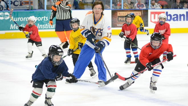 """Steve Carlson from the 1977 hockey movie """"Slap Shot"""" skates with youth players between periods of an American Hockey League game between the Milwaukee Admirals and Charlotte Checkers on Friday at the UW-Milwaukee Panther Arena."""