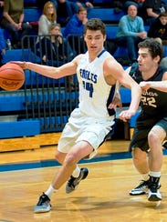 Lakeland's Cody McComas (left) goes with the high dribble