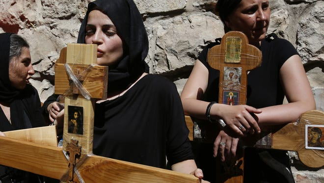 A Christian Orthodox pilgrim kisses a wooden cross as she and others carry them along the Via Dolorosa (Way of Suffering) during a procession marking Good Friday on April 18 in Jerusalem's Old City.